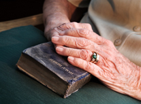 manifesting  money - old hands on Bible